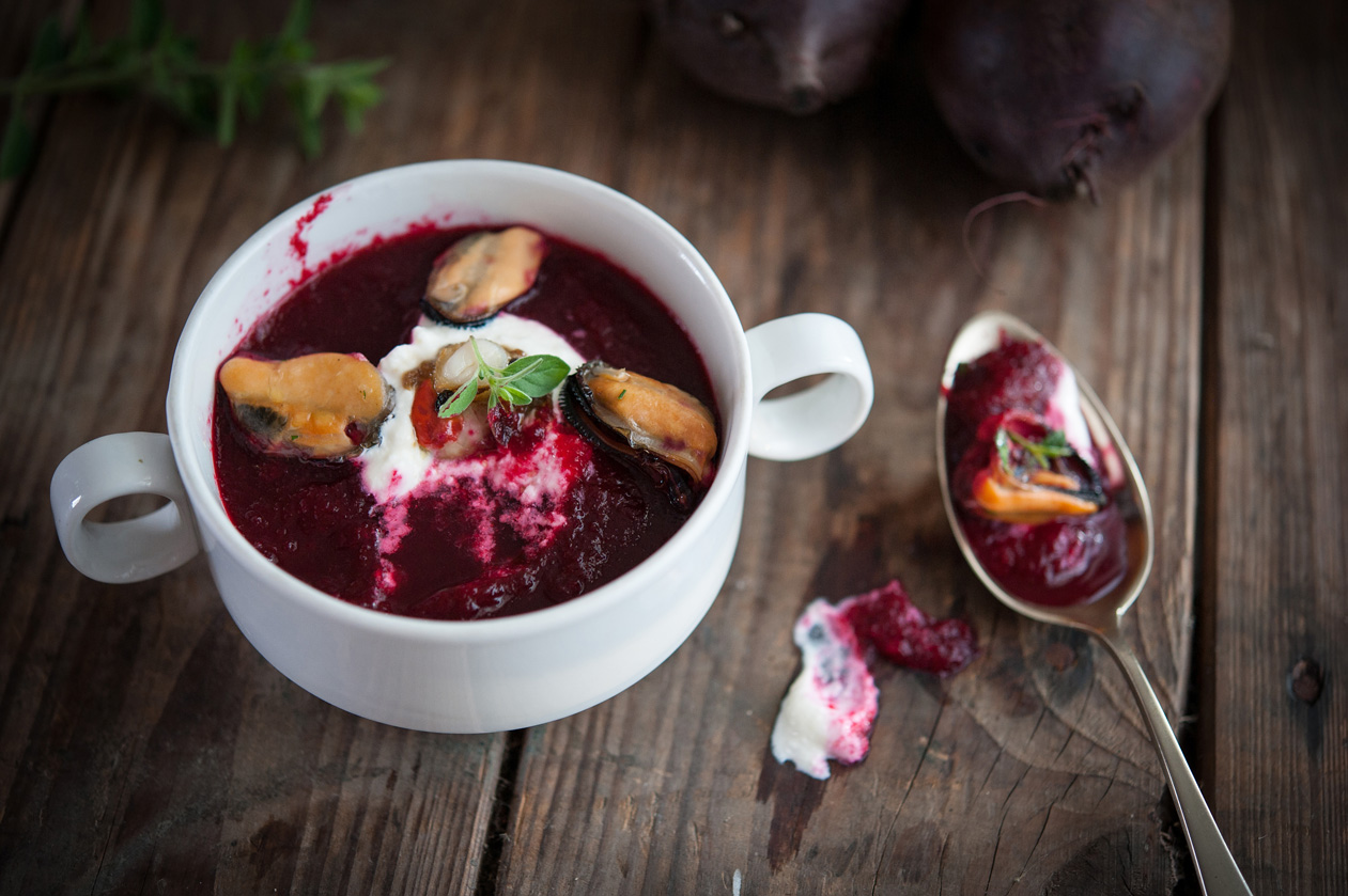 beetroot soup with mussels, sour cream and fresh oregano on a wood table, composition with spoon