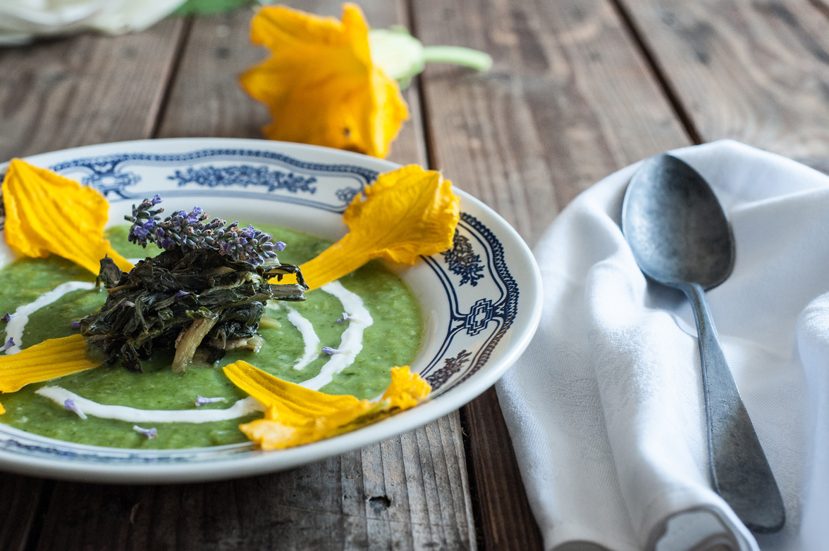 zucchini soup with stuffed green vegetables, fresh lavander and zucchini flowers sour cream. Props: iron spoon and wooden table