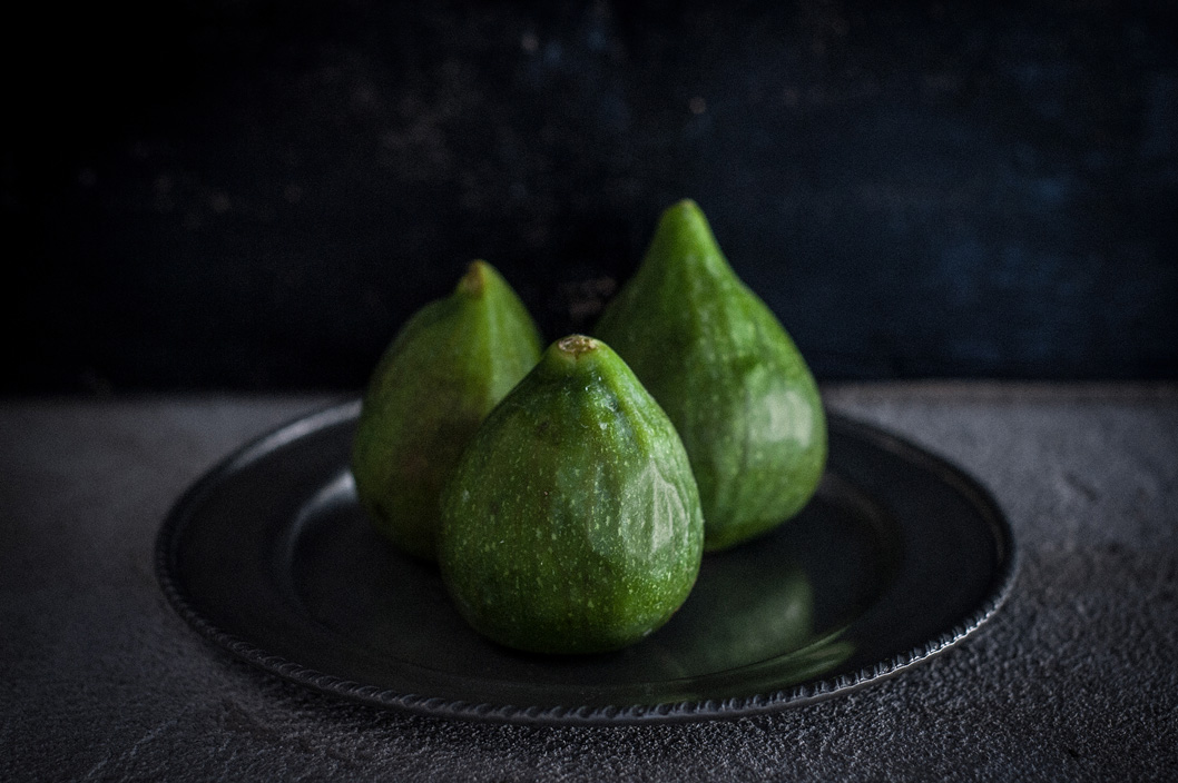 green figs on an iron dish with low natural light